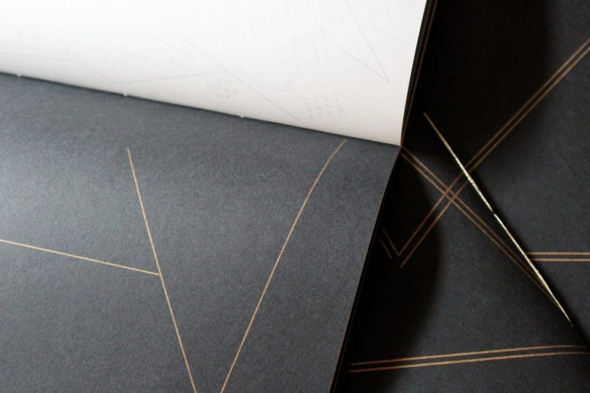 """Image: Udita Upadhyaya's book """"nevernotmusic"""" (detail). Part of one page-spread is visible, with opaque black paper on one page (on which three thin gold lines touch to form large open triangles) and with whitish vellum on the other page (with lines, open triangles, and letters printed on the other side of the sheet of vellum, and slightly visible through it). In the background, beyond this copy, is part of the front cover of two other copies, with gold stitching and straight gold lines on black paper. Photo by Caleb Neubauer."""