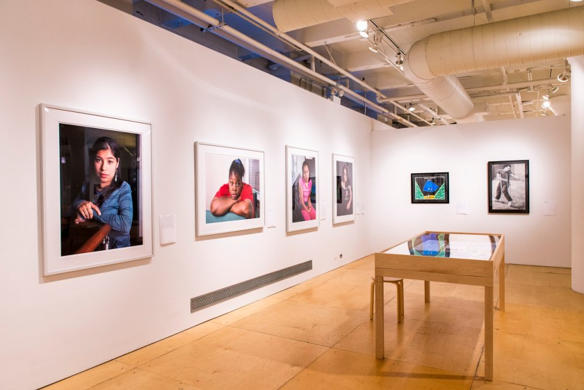 Image: a view of two gallery walls featuring primarily large format photography portraits; to the right is a display table with printed ephemera. Photo by Ryan Edmund.