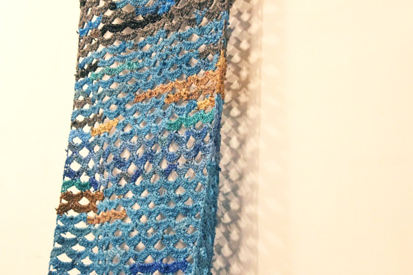 "Image: Detail of a crocheted piece by Jerry Bleem, which was created as part of a performance in response to Udita's score, ""Dear Jerry and Nick: Hold (a hand a spine a heart a whole self)."" The piece is made of blue, grey, brown, and black plastic bags. The crocheted pattern appears like a series of connected crescents, with the white wall visible behind the artwork and through the gaps between the crescents (in turn, casting patterned shadows on the wall). Photo by Caleb Neubauer."