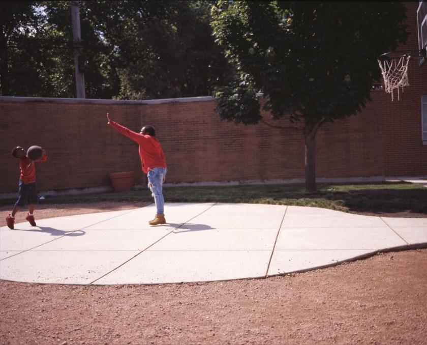 Image: A child in a long-sleeved red t-shirt and matching gym shoes shoots a jumper over the outstretched arm of a slightly older child in a red hoodie and wheat boots in the courtyard of BBF Family Services. Photo by Eric K. Roberts.