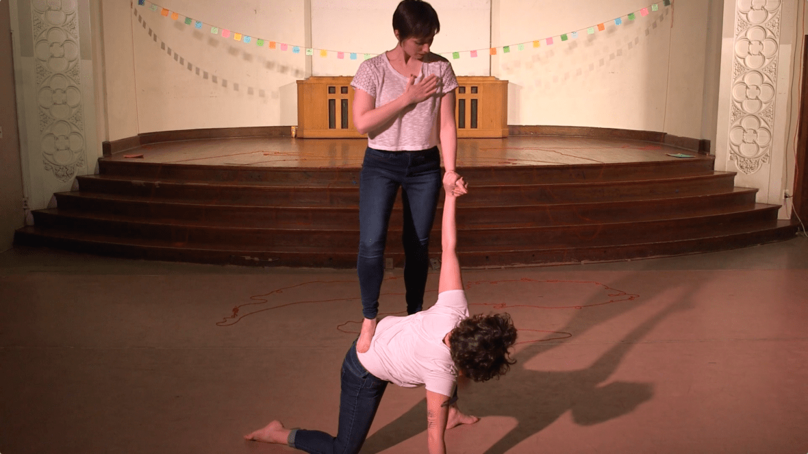 """Featured image: Maggie Robinson and Allison Sokolowski performing in """"I Am"""" at the Chicago Danztheatre Auditorium, as part of the Body Passages culminating event. Maggie balances with one foot, knee, and hand on the floor, as Allison stands on Maggie's lower back. The performers hold each other's left hands and look at each other. Both are barefoot and wear white t-shirts and jeans. Behind them is a well-lit stage, with a string of colorful paper suspended across it. Still from a video by John Borowski."""