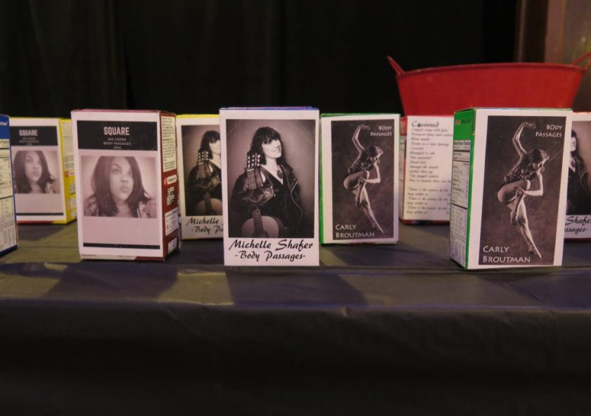"Image: The interactive installation related to Carly Broutman, Jeanette ""Jae"" Green, and Michelle Shafer's performance ""Wax."" This is a close-up image of a table with a black tablecloth, on which several single-serving cereal boxes sit, each stickered on one side with a black-and-white photograph of a group member. Visible in the background are the back of one box, including lyrics for ""Cocooned,"" and a red bucket. Photo by Marya Spont-Lemus."