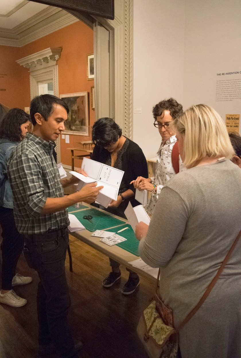 Image: Regin Igloria (at left, in plaid shirt) shows visitors how to make simple artist books, during the opening night of the Participatory Arts: Crafting Social Change exhibition. He is surrounded by a group of people, and between them is a table with paper and various tools for bookmaking. Photo courtesy of Jane Addams Hull-House Museum / Jesse Meredith.