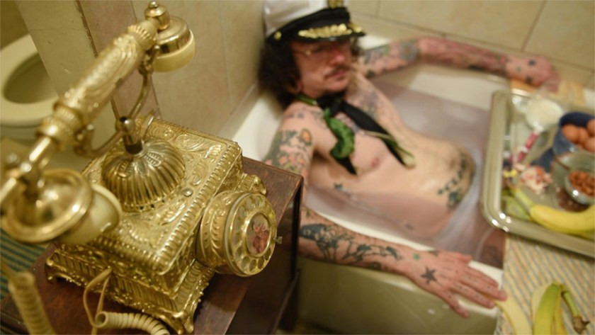 "Image: Film still from ""Sextra Curricular Activity"", featuring actor Jack W. Cooper. In this scene, Jack's character receives a prank phone call while taking a hot soak in the tub and enjoying some light snacks. Photo courtesy of Heather Raquel Phillips."