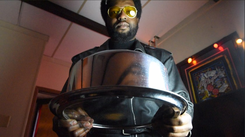"""Image: Film still from """"Thirst Trap"""" featuring actor Blackson leaning forward in preparation to serve his queen cake from a stainless steel cake carrier. Photo courtesy of Heather Raquel Phillips."""