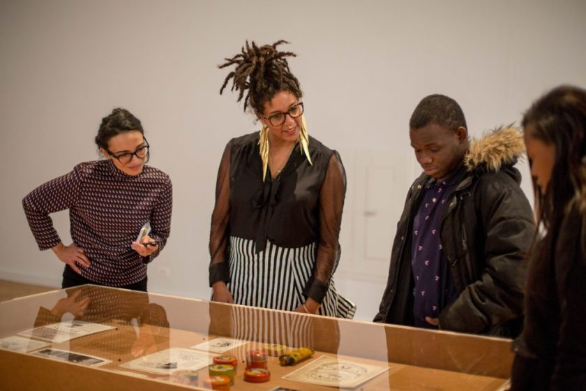 """Image: The author, D. Denenge Duyst-Akpem, and two young visitors look at beauty product containers and printed materials displayed in a vitrine in the """"African American Designers in Chicago"""" exhibition at the Chicago Cultural Center. Photo by Ireashia Bennett."""