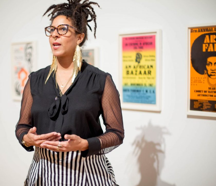 """Image: D. Denenge Duyst-Akpem speaking while visiting the exhibition """"African American Designers in Chicago"""" at the Chicago Cultural Center. Duyst-Akpem stands in front of colorful posters advertising theatrical and musical performances in Chicago. Photo by Ireashia Bennett."""