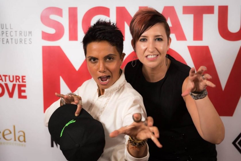 """In this medium shot, Fawzia and Lisa pose in front of a white wall emblazoned with the red """"Signature Move,"""" grey Full Spectrum Features, and other logos. Both Fawzia and Lisa look at the camera with playful snarls and with fingers bent like cat claws. Fawzia wears a long-sleeved white button-up and, in one hand, holds a black baseball cap with neon green detailing. Lisa wears a black sleeveless shirt. Both wear multiple bracelets and rings."""