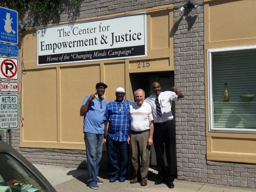"""Image: Danny Franklin and three other men stand on the sidewalk outside """"The Center for Empowerment & Justice: Home of the 'Changing Minds Campaign.'"""" Photo courtesy of Michael Fischer."""