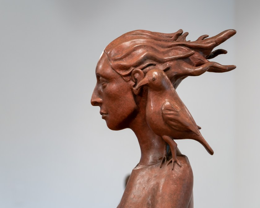 """Image: Patricia Whalen Keck """"The Pedestrian"""" (Detail) Bronze. Profile of a woman with her hair blowing behind her with a bird placed upon her shoulder. Photo Courtesy of the Artist."""