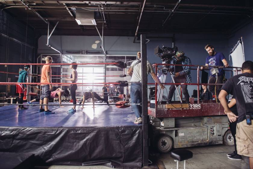 "This image shows the film ""Signature Move"" in production in a large open room with exposed piping. On the left-hand side of the image is a fighting ring, in which Zaynab (played by Fawzia Mirza) and other characters in workout clothes stretch and talk. Zaynab wears a tight green hoodie with red and white shorts over black tights. On the right-hand side of the image are members of the production crew, who are operating the camera, holding wires, or looking on. The camera operator and another person stand on a scissor lift with the camera and camera tripod."