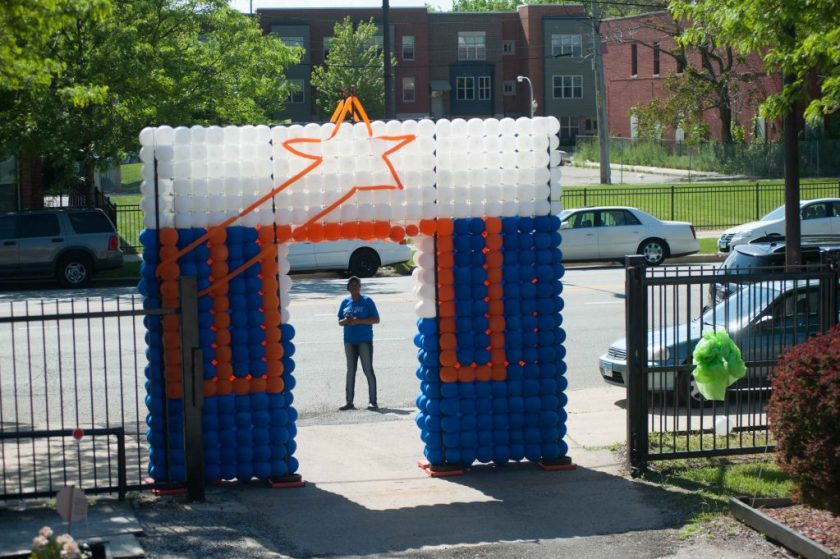 A photo from the Bright Star block party in summer 2018. There is a balloon arch made in the design of the Bright Star blue, orange, and white logo. There is a person standing just behind the threshold on the street in front of the arch. Photo by Tony Smith.