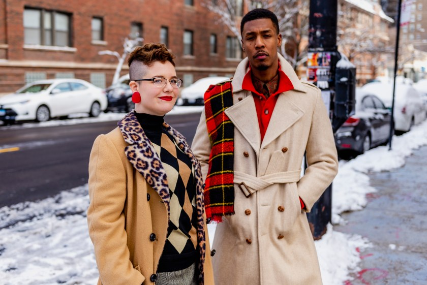 Image: Two models are seen posing on the sidewalk on 55th street outside of Gilda's. There is snow and cars in the background. The pair are looking directly into the camera. The person on the right has on a beige coat with a red-checkered scarf and red shirt. The person on the left has a brown coat on with buttons and a leopard collar. Their shirt is brown, beige, and black. Photo by Ryan Edmund Thiel.