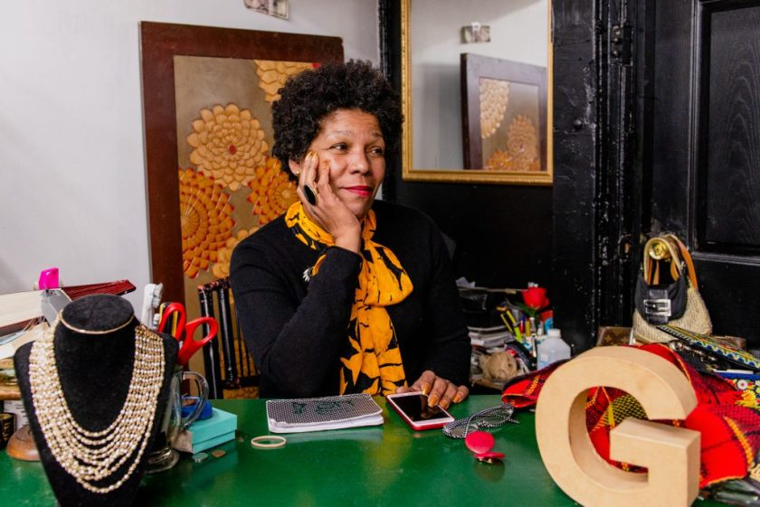 "Image: Gilda Norris is seated at her desk wearing a black shirt and a yellow and black scarf. She has her chin in her hand and is looking off towards the right portion of the photo. There are items on her green desk: a wooden ""G,"" a gold necklace, her iPhone, a notepad, pens, and scissors. In the background, there is a framed image of yellow and orange flowers and a mirror. Photo by Ryan Edmund Thiel."