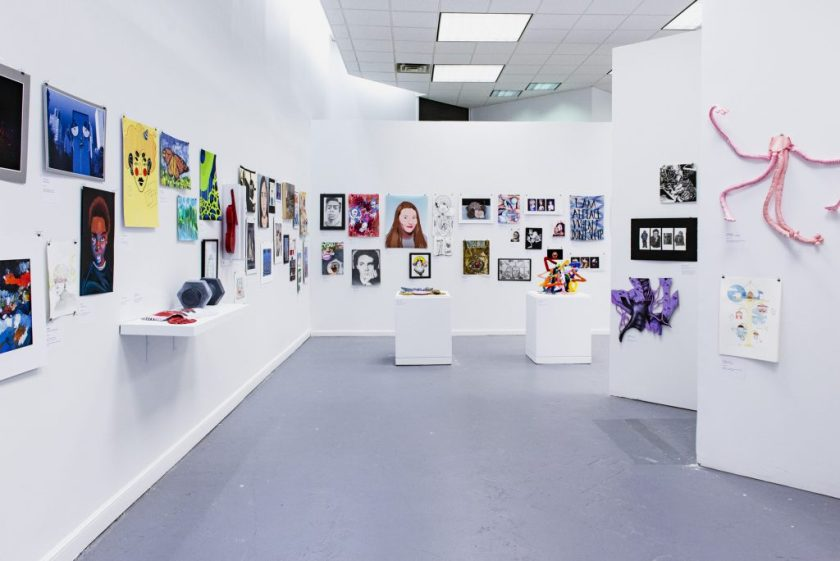 Image: Partial view of the exhibition. Various artworks of different styles, sizes, and colors are displayed on the walls and upon pedestals. Photo by Ryan Edmund.