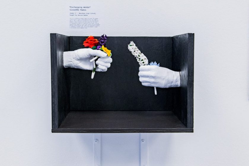 """Image: Gisselle Ramos, """"Exchanging Words"""". A black wooden box containing white porcelain hands outreached toward one another, each holding delicate flowers. The hand on the left is positioned higher than the right. Photo by Ryan Edmund."""