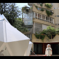 Image: Video still from Hương Ngô's, In the Shadow of the Future, 2014-19. Still shows someone dressed up in a cosmonaut outfit standing in the foreground next to a large white geometric structure. In the background is a building with plants dangling out the windows, with architecture in a similar triangular style as the white structure as well as Hương's central installation. It is a sunny day out in the photo. Image courtesy of the artist.
