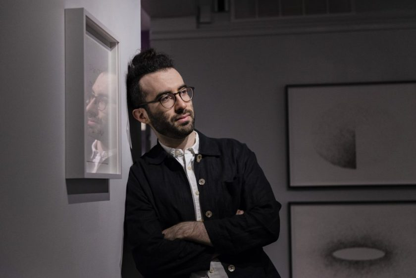 "Image: The artist is leaning against a gallery wall in the LA&M. He is looking off towards the right side of the space, his arms are crossed, and he is wearing a dark button down. He has glasses and a beard. His facial reflection can be seen in a piece that is hanging on the left hand side in a frame. Two ""hair drawings"" can be seen, out of focus, in the back of the gallery. Photo by Ryan Edmund Thiel."