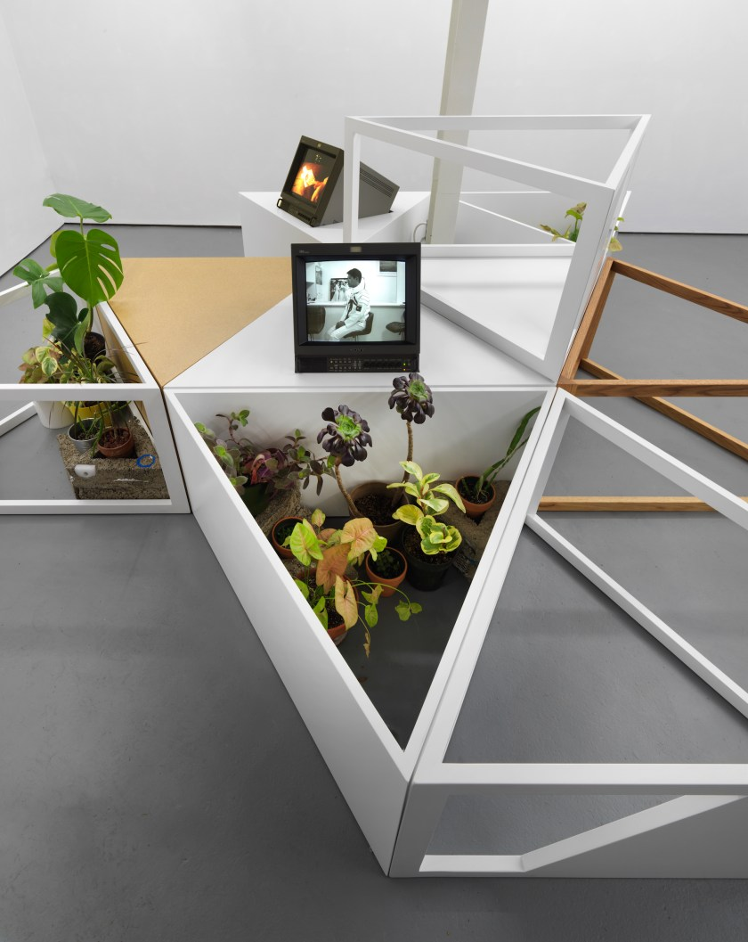 Image: Photo of multiple white and brown wooden triangle segments joined alongside each other, with one stacked on top. Two segments in the foreground hold varied amounts of potted plants with green, purple, and yellow leaves. Set on the top of one segment is a TV screen directly facing the viewer. The screen shows black and white image of a cosmonaut sitting sideways on a chair in a space suit without a helmet. In the background, a second TV is faced at an angle and tilted upwards displaying a yellow, red, and black image. Image courtesy of artist.