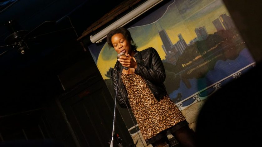 Image: Photo of Britt Julious performing on-stage at Miss Spoken at the Gallery Cabaret. Julious stands on-stage, speaking into the microphone while looking at a phone. Julious wears a black jacket over an animal-print dress with black trim. The reader appears in medium-long-shot at the center side of the frame, which is skewed at a diagonal. Painted on the stage wall behind the reader is a scene showing Chicago's skyline, as if viewed from behind a stone wall. Photo by Sarah Joyce. Courtesy of Miss Spoken.
