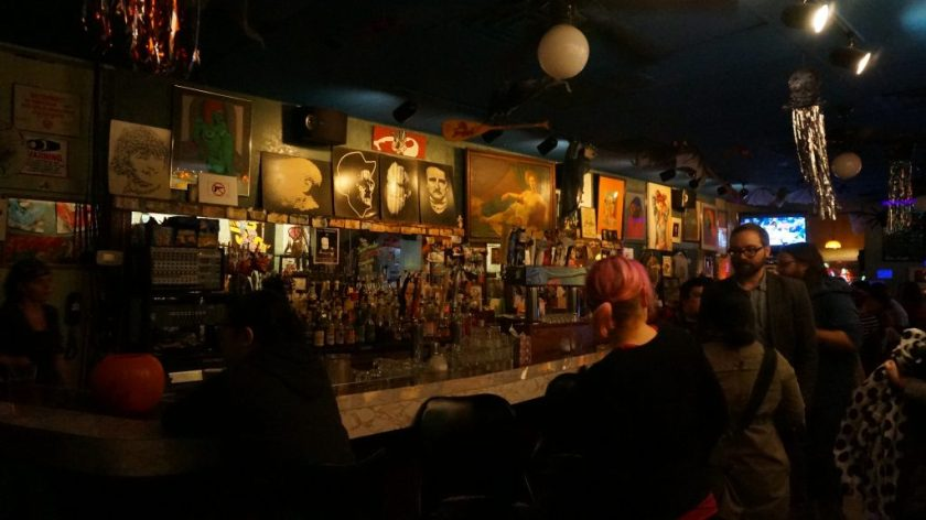 Image: Photo of the bar area at Miss Spoken at the Gallery Cabaret. Lining the wall along the back of the bar area are several drawings, paintings, and photographs. Most images show faces and/or bodies, but are otherwise diverse, reflecting a range of styles, ages, color palettes, etc. Objects like oars and metallic streamers hang from the ceiling. In the foreground, patrons mingle in the dim bar. Photo by Sarah Joyce. Courtesy of Miss Spoken.