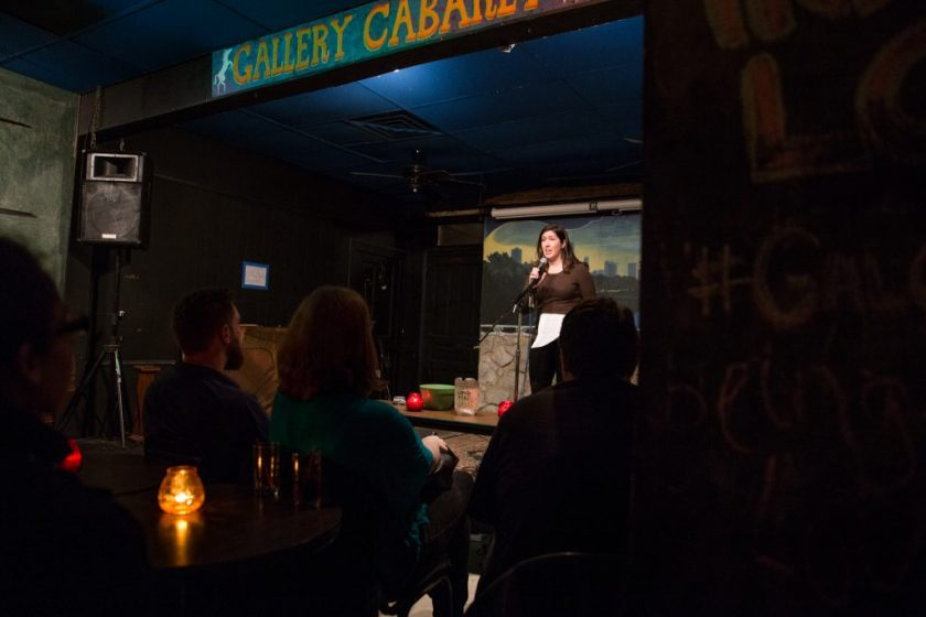 """Image: Photo of Gina Watters performing at Miss Spoken at the Gallery Cabaret. The reader, wearing a dark shirt and dark pants, stands on-stage speaking into the microphone while looking out at the audience. One of Watters' hands grips the microphone and the other holds loose papers. The reader appears small near the center of the frame. Painted on the stage wall behind the reader is a scene showing Chicago's skyline, as if viewed from behind a stone wall. In the foreground, the words """"Gallery Cabaret"""" are partially visible at the top of the frame. The backs and sides of some audience members' heads are visible at the bottom of the image. Photo by Sarah Joyce. Courtesy of Miss Spoken."""