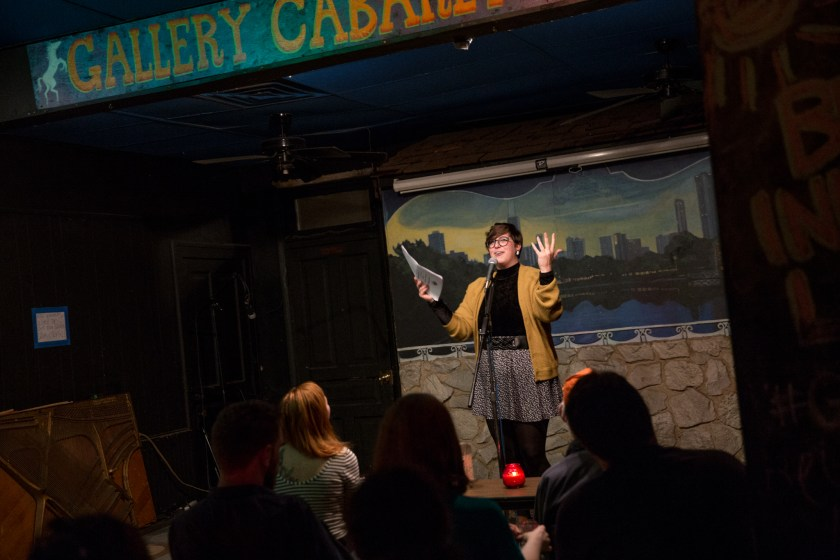 """Image: Photo of Brittany Meyer performing at Miss Spoken at the Gallery Cabaret. The reader stands on-stage, smiling and speaking into the microphone while looking out at the audience. Meyer's hands are raised in expression; one hand holds loose papers and the other is open. Meyer wears a mustard-gold cardigan open over a black turtleneck, a dark patterned skirt over dark leggings, and glasses. The reader appears small near the center of the frame. Painted on the stage wall behind the reader is a scene showing Chicago's skyline, as if viewed from behind a stone wall. In the foreground, the words """"Gallery Cabaret"""" are partially visible at the top of the frame and the backs of some audience members' heads are visible at the bottom. Photo by  Sarah Joyce.  Courtesy of Miss Spoken."""