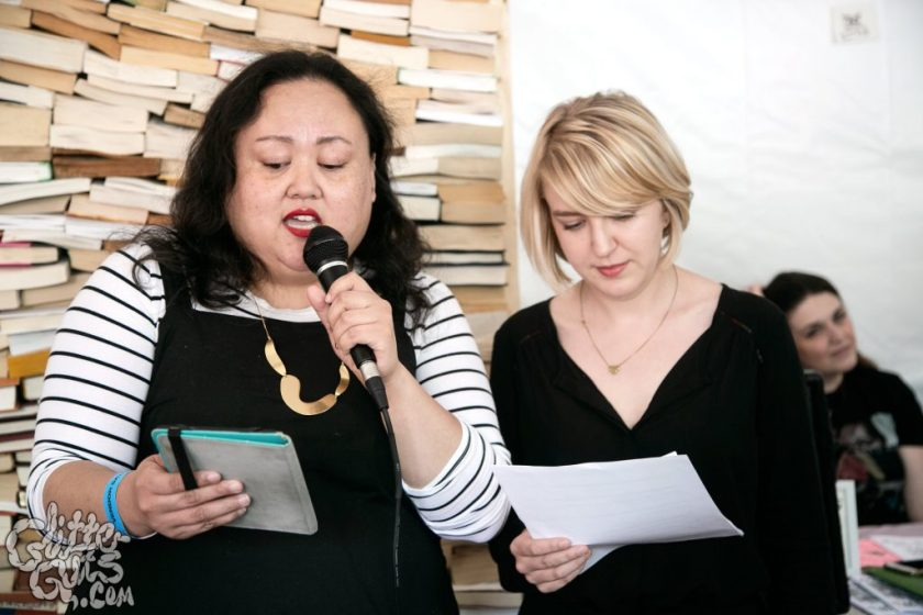 """Image: Photo of Jasmine Davila (left) and Rosamund Lannin (right) standing in front of a giant wall of hardcover and softcover books. The books are stacked floor to ceiling so that each book's top or bottom edge is visible but its spine is not. Together, the pages create a mosaic of white, tan, and light brown rectangles. Davila holds a microphone and reads off a tablet. Lannin looks down at loose papers in her hand. Davila wears a black jumper over a white and black striped shirt, and Lannin wears a black shirt. A logo reading """"GlitterGuts.com"""" is superimposed in the bottom left-hand corner. Photo by GlitterGuts. Courtesy of Miss Spoken."""