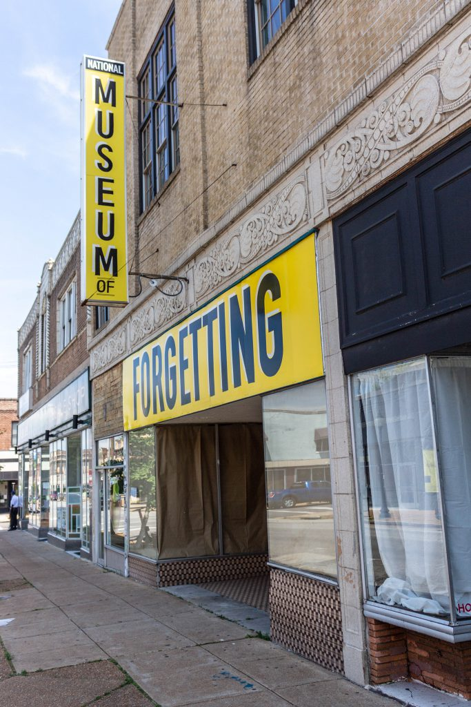 """Image: Joseph del Pesco and Jon Rubin, Monuments, Ruins and Forgetting; 2019. Installation with changing signpainting. A vacant storefront has two large yellow sign that together reads """"The National Museum of Forgetting."""" Photo by Shabez Jamal."""