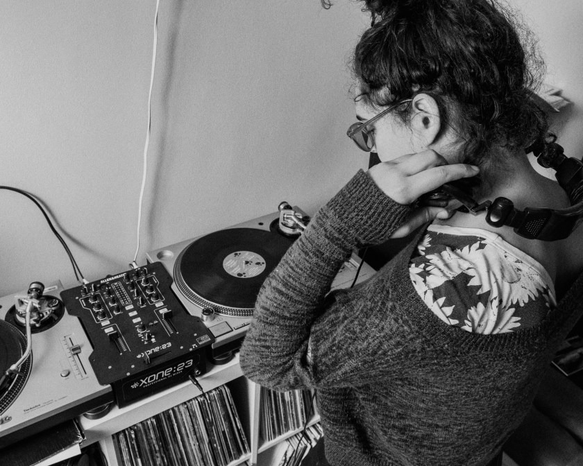 Image: In a black-and-white photo, Ariel looks down at the turntables and mixer that sit on a shelf full of records in her living room. Photo by Ryan Edmund.