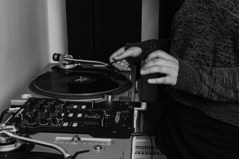 Image: Ariel places the needle on a record in a black-and-white photo. Photo by Ryan Edmund.