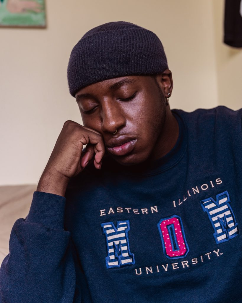 "Image:Miss Twink USA closes his eyes and rests his chin on his fist. He's wearing a beanie and a navy blue sweatshirt that reads, ""Eastern Illinois University Mom."" Photo by Ryan Edmund."