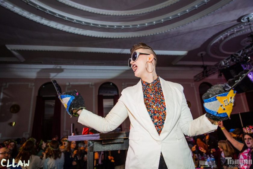 """Image: Chelsea Fiddyment as Sir Elton Brawn, celebrating a championship win at CLLAW XXXII (Chicago League of Lady Arm Wrestlers), at Logan Square Auditorium in 2019. The camera looks up at Fiddyment from the vantage-point of the audience. Fiddyment is well-lit in the middle of a large, dim room that has high windows and a white ceiling with ornamental mouldings. Behind Fiddyment, dozens of the audience members are partially visible, most cheering and wearing sparkly headwear. On each hand, Fiddyment wears a large foam fist, with the middle finger raised, and Fiddyment stands with arms out, as if giving the middle finger in celebration to both sides of the room. Fiddyment's mouth is open as if yelling, and an artificial, painted gap is visible between Fiddyment's two front teeth. Fiddyment wears sparkly sunglasses, a light-colored sportcoat, and a bright, floral-print shirt buttoned to the top. The image has logos for """"CLLAW"""" and """"Trainman Photography"""" in its bottom corners. Photo by Trainman Photography. Courtesy of the artist."""