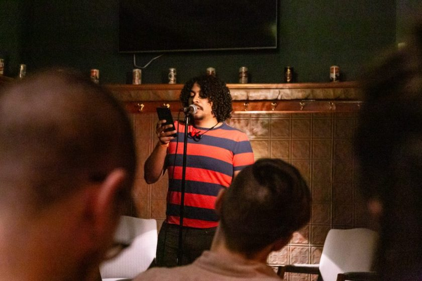 Image: Michael Tucker performing at Unreal at Schubas. Tucker stands at the front of the room, speaking into a microphone while reading off a phone. Behind Tucker is a copper-colored wall, made of a grid of low-relief tiles; above that are several decorative beer cans on a ledge, a dark green section of wall, and a flat-screen monitor. Tucker wears a red and blue striped tee with jeans. The backs of some audience members' heads are unfocused in the foreground. Photo by Joshua Clay Johnson.