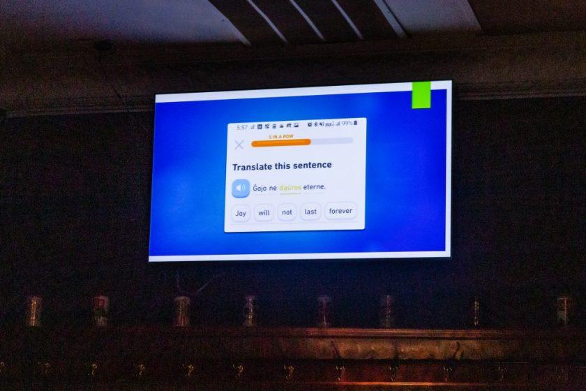 """Image: An excerpt of a piece by Jerliyah Craig (not present), comprised of presentation slides being advanced by Chelsea Fiddyment (out of frame) at Unreal at Schubas. Against a blue background, this slide shows a phone screenshot of a translation activity from the app Duolingo, with the same sentence in Esperanto (""""Ĝojo ne daŭros eterne"""") and English (""""Joy will not last forever""""). The slides are being presented on a flat-screen monitor, above and below which parts of the wall and ceiling are visible. The room's lights are off. Photo by Joshua Clay Johnson."""