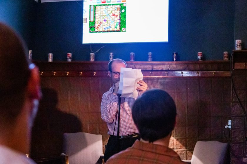 Image: John Pinkus performing at Unreal at Schubas. Pinkus stands at the microphone at the front of the room, face partially blocked by a creased paper. Above and behind Pinkus, on the wall, is a flat-screen monitor showing an internet-based game of Snakes and Ladders (being played for Pinkus by Chelsea Fiddyment, out of the frame). Also behind Pinkus is a copper-colored wall, made of a grid of low-relief tiles, and a door; above that are several decorative beer cans on a ledge and a dark green section of wall. Pinkus wears a white, blue, and orange collared shirt and dark-rimmed glasses. The back of some audience members' heads are unfocused in the foreground. Photo by Joshua Clay Johnson.
