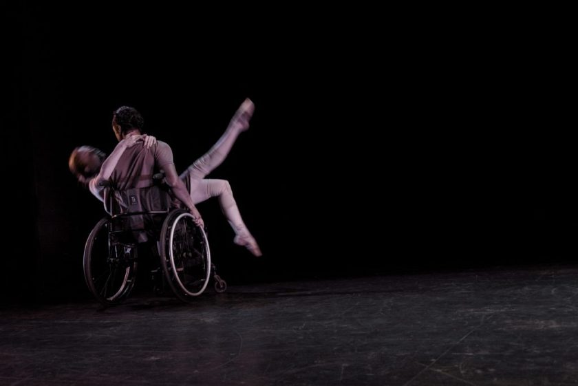 Image: Two dancers dressed in light grey clothing are in motion on a dark stage; one dancer (Julia Cox) reclines in the lap of the other dancer (Robby Williams), with her legs pointed expressively into the air; her partner is seated in an active wheelchair with his back to the camera. Photo by Ryan Edmund.