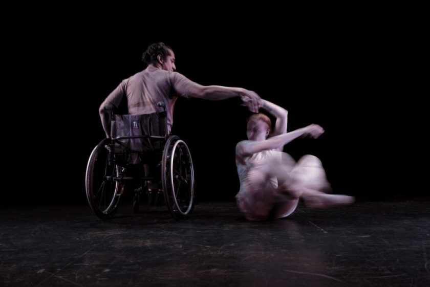 Image:  Two dancers dressed in light grey clothing are in motion on a dark stage; the dancer on the left (Robby Williams) is seated in an active wheelchair with his back to the camera; the dancer on the right (Julia Cox) spins on the floor, with the help of her partner. Photo by Ryan Edmund.