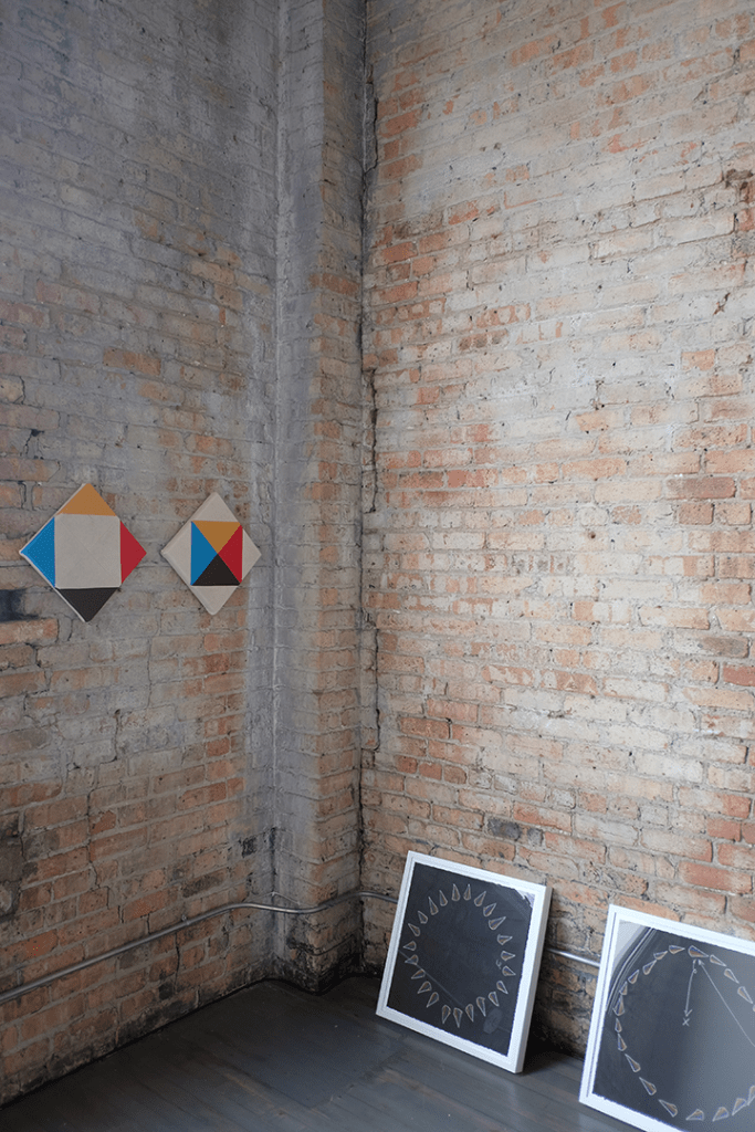 """Image: The corners of a fading brick room meeting. On the left, about five feet off the ground are two canvases with an inch between them. These are Paolo Arao's """"Greater Than (Diptych)"""" Leaning against the brick wall to the right on the floor are two of Jeffery Augustine Songco's """"Choreography Playbook"""" series. Image courtesy of FLXST Contemporary."""