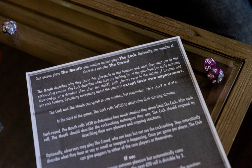 """Image: A close up of a piece of paper with a black background and white text explains the game, """"Welcome to Paradise, Baby"""" where one player is The Mouth, the other player is The Cock and observers, like our staff photographer, was The Crowd. To the right side of the paper are two die. Photo by Ryan Edmund Thiel"""