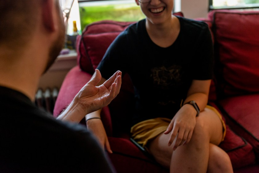 "Image: The viewer is looking over the artists shoulder as he makes a hand gesture that resembles a ""cupping"" motion. Across from the artist is his roommate, their legs are crossed with one arm resting on their left leg. The top half of their face is out of the frame but their bottom half is laughing. Photo by Ryan Edmund Thiel."