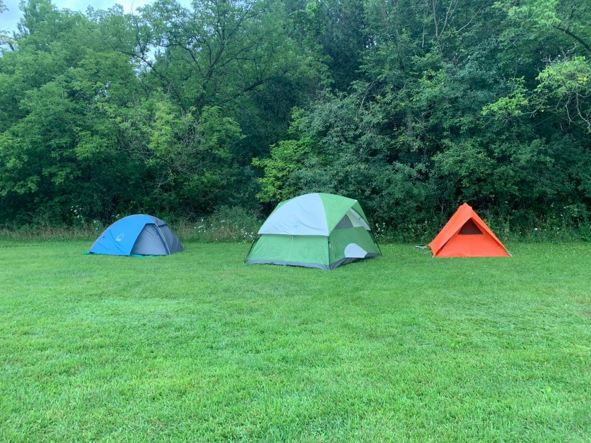 Image: Outdoor scene with three tents (blue, green, and orange) set up on a grass lawn in front of a line of trees. Photo courtesy of Maeve Jackson.