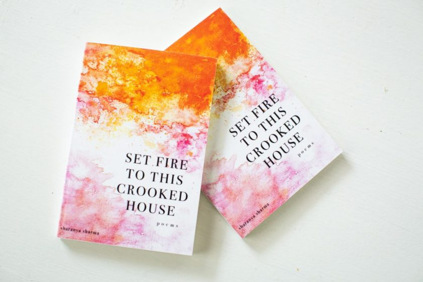 "Image: Two copies of Sharanya Sharma's MFA thesis, a poetry collection entitled ""Set Fire to This Crooked House."" The thesis is bound with a colorful cover, on which orange and pink watercolors fade into each other and into white. The title appears in all capital letters and the words ""poems"" and ""sharanya sharma"" in all lower-case. Photo by Kristie Kahns Photography."