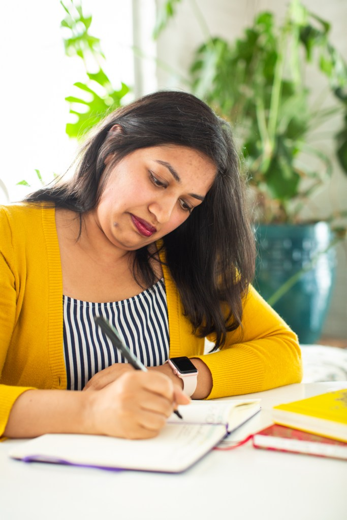 Image: Sharanya Sharma. Sharma sits at a white table, looking down at an open notebook. Sharma holds a pen poised above the paper. Sharma wears a marigold cardigan open over a black and white striped shirt. Behind Sharma is a large plant, and natural light comes through the windows. Photo by Kristie Kahns Photography.