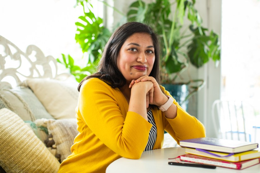 Image: Sharanya Sharma. Sharma sits with hands under chin and elbows on a white table, next to a pile of multi-colored notebooks. Sharma wears a marigold cardigan open over a black and white striped shirt and looks at the camera with a slight smile. Behind Sharma are several pastel throw pillows and a large plant, and natural light comes through the windows. Photo by Kristie Kahns Photography.