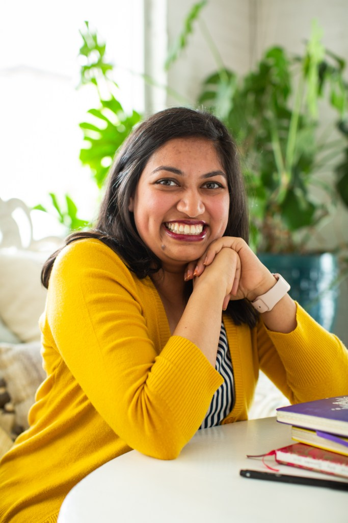 Image: Sharanya Sharma. Sharma sits, leaning on one hand, elbow on a white table next to a few multi-colored notebooks. Sharma wears a marigold cardigan open over a black and white striped shirt and smiles at the camera. Behind Sharma is a large plant, and natural light comes through the windows. Photo by Kristie Kahns Photography.