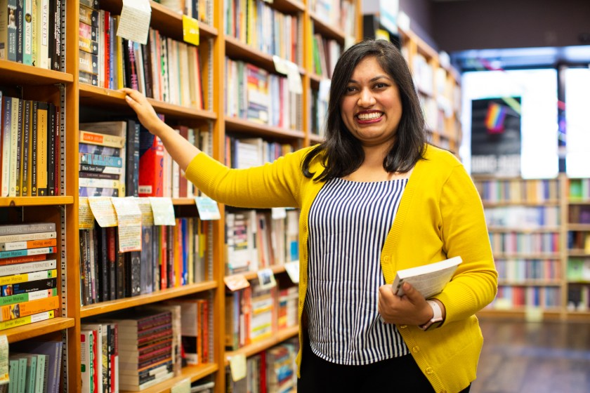 Image: Sharanya Sharma. Sharma stands inside a bookstore, smiling at the camera, with one hand holding a book and the other hand resting on a shelf. Sharma wears a marigold cardigan open over a black and white striped shirt, with black pants. The bookstore is bright with daylight. A long, tall set of shelves occupies most of the background. Photo by Kristie Kahns Photography.
