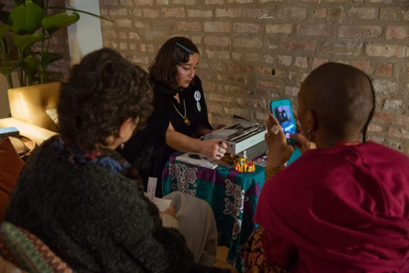 """Image: In-Session, at Threewalls in November 2018, by Najee Searcy and collaborators, in response to the guiding work """"Hush: Don't Say Anything to God: Passionate Poems of Rumi"""" by Shahram Shiva. Melissa Castro Almandina sits at a small table that is covered in a colorful tablecloth, looking down at a typewriter while turning the knob to advance paper through it. Also on the table is a copy of Claudia Rankine's book, """"Citizen: An American Lyric,"""" and small sculptural objects that are primarily yellow, brown, and red. The artist wears a similar object as a pendant. The artist wears black clothes, as well as multi-colored rings, buttons, and hair clips. In the foreground, with their backs to the camera, sit two people, one using a phone to take a photo of the artist and the other holding slips of paper with text on them. Photo by Milo Bosh. Courtesy of Threewalls."""