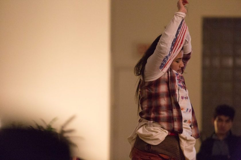 """Image: In-Session, at Threewalls in February 2018, by Jose Luis Benavides and collaborators, in response to the guiding work """"Mexican American Disambiguation"""" by José Olivarez. In this medium shot, a participant is in the act of dressing or undressing, pulling a white shirt with a U.S. American flag pattern over their head. The participant's arms are in the air, entangled in the shirt, and underneath it the participant wears several tops and bottoms. One audience member is fuzzy in the background with, possibly, one in the foreground. Photo by Milo Bosh. Courtesy of Threewalls."""