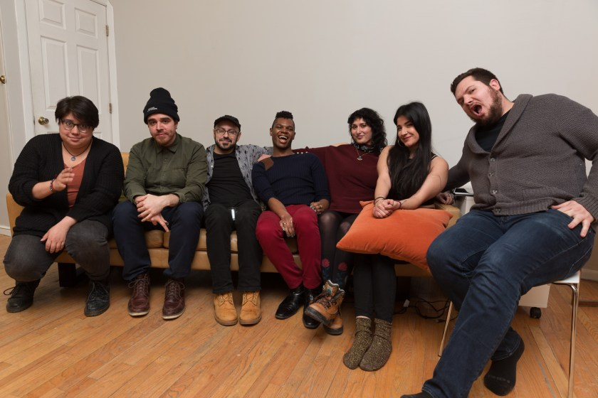 "Image: In-Session, at Threewalls in February 2018, by Jose Luis Benavides and collaborators, in response to the guiding work ""Mexican American Disambiguation"" by José Olivarez. After the performance and discussion, Regina Martinez (third from right) and six others (performers) sit together on or near a tan couch, smiling or making faces at the camera. Martinez wears a maroon top with dark leggings and boots. Photo by Milo Bosh. Courtesy of Threewalls."